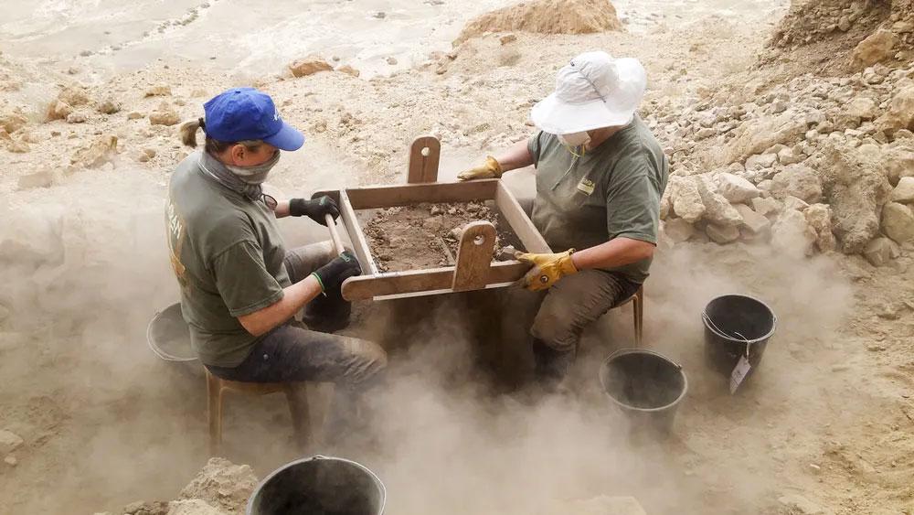 Des étudiants de l'Institut d'archéologie de l'Université hébraïque de Jérusalem, filtrant des dépôts provenant d'une grotte sur les falaises à l'ouest de Qumrân, près de la rive nord-ouest de la mer Morte, en Israël, en 2017.